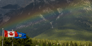 large mountains in the background with a rainbow stretching across the image seemingly coming right out of a Canadian flag