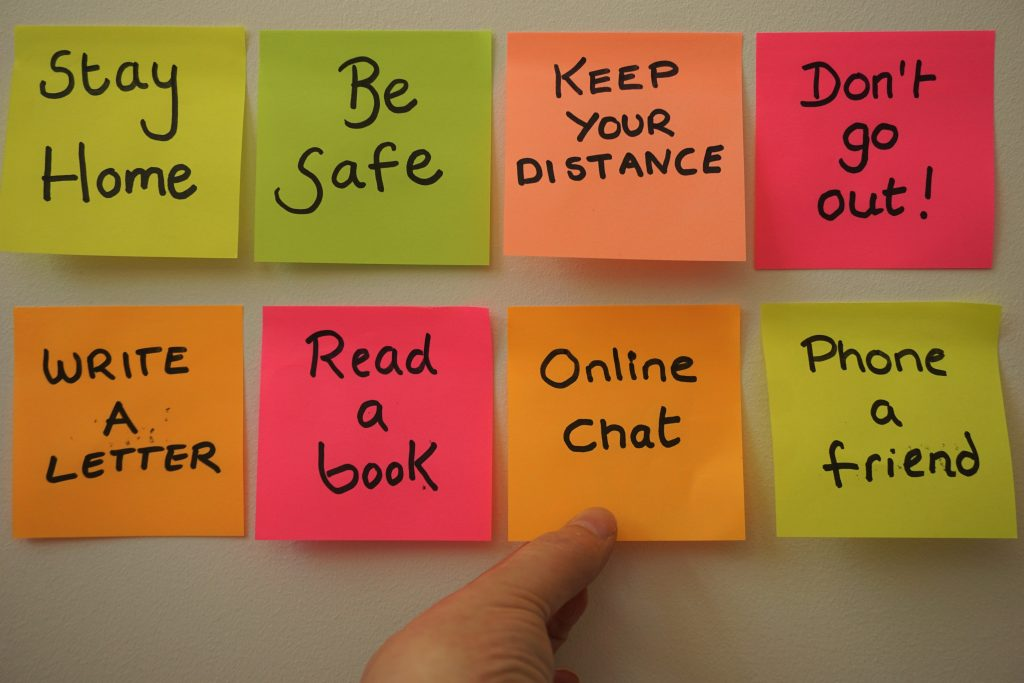 colourful post-it notes encouraging people to stay home and be safe; keep your distance; don't go out; online chat; write a letter; phone a friend